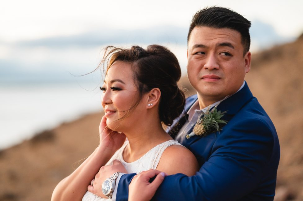 Newlyweds embrace on a ridge at Coyote Hills Regional Park