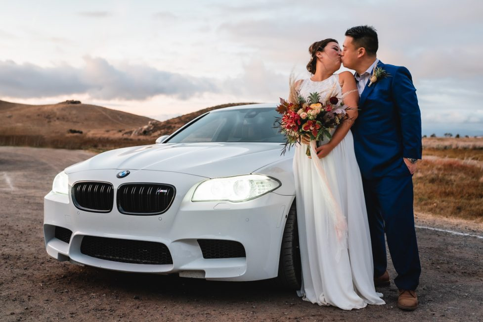 Newlyweds kiss in front of a BMW M5 automobile at Coyote Hills Regional Park.