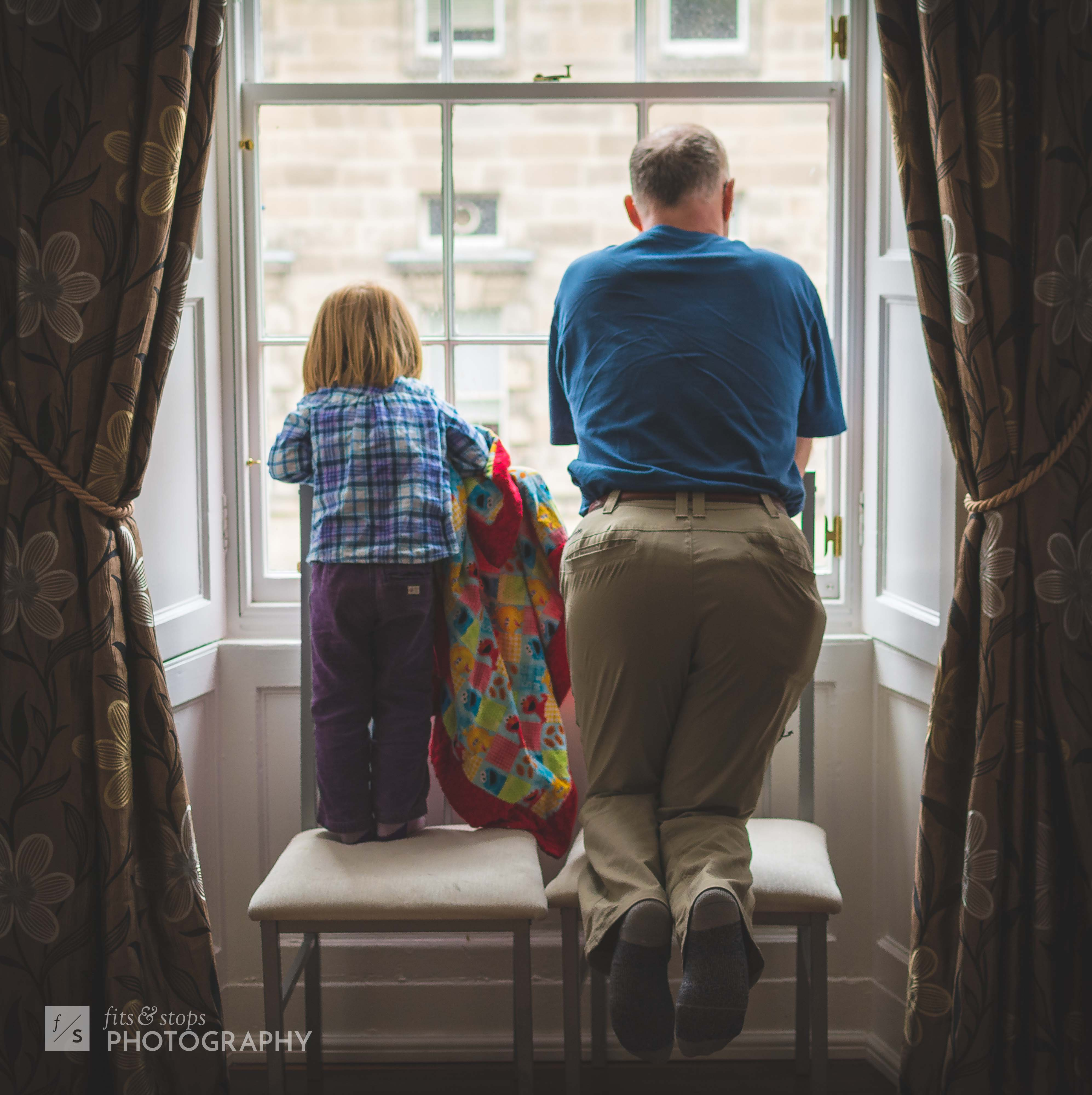 A little girl and her grandfather peer out a second-story window down to Edinburgh's Royal Mile,
