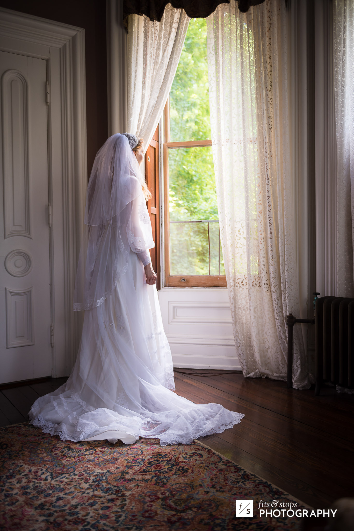 A bride stands near the window light into her bedroom.