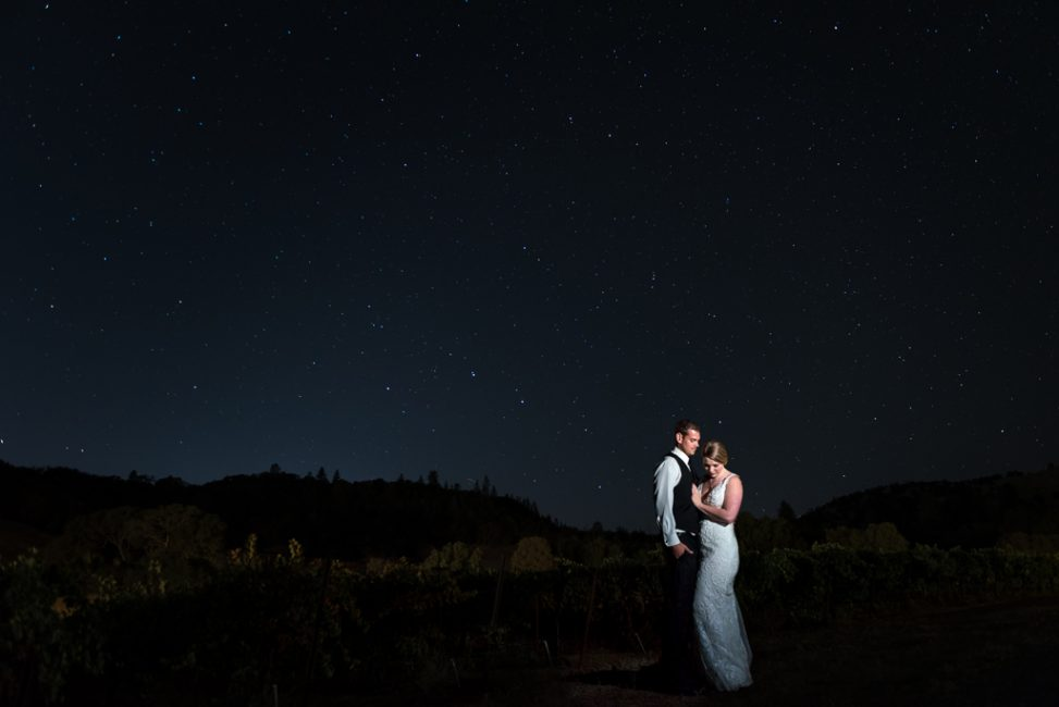 A bride and groom stand beneath the stars at their foothills wedding