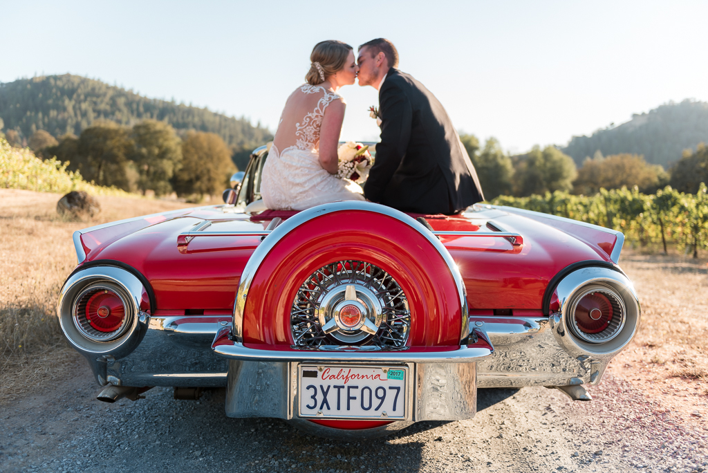 A bride and groom kiss atop a vintage Thunderbird at their foothills wedding
