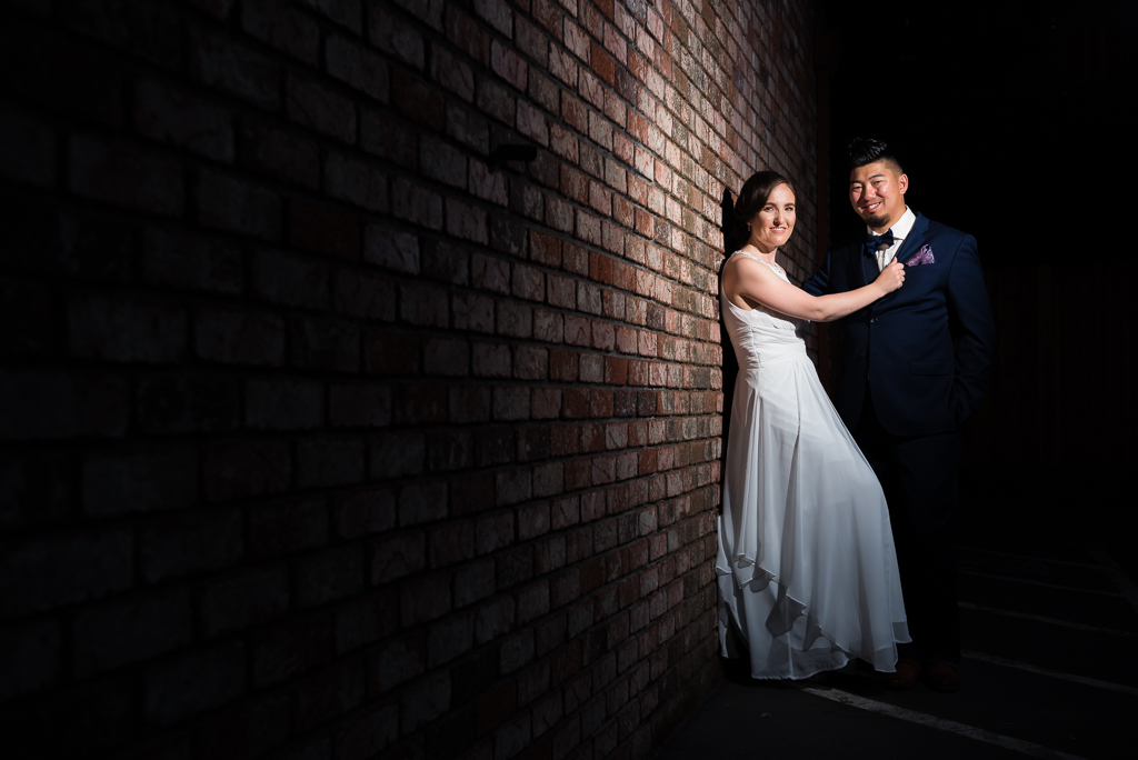 A bride and groom pose against a brick wall during their hometown wedding in Elk Grove, CA.