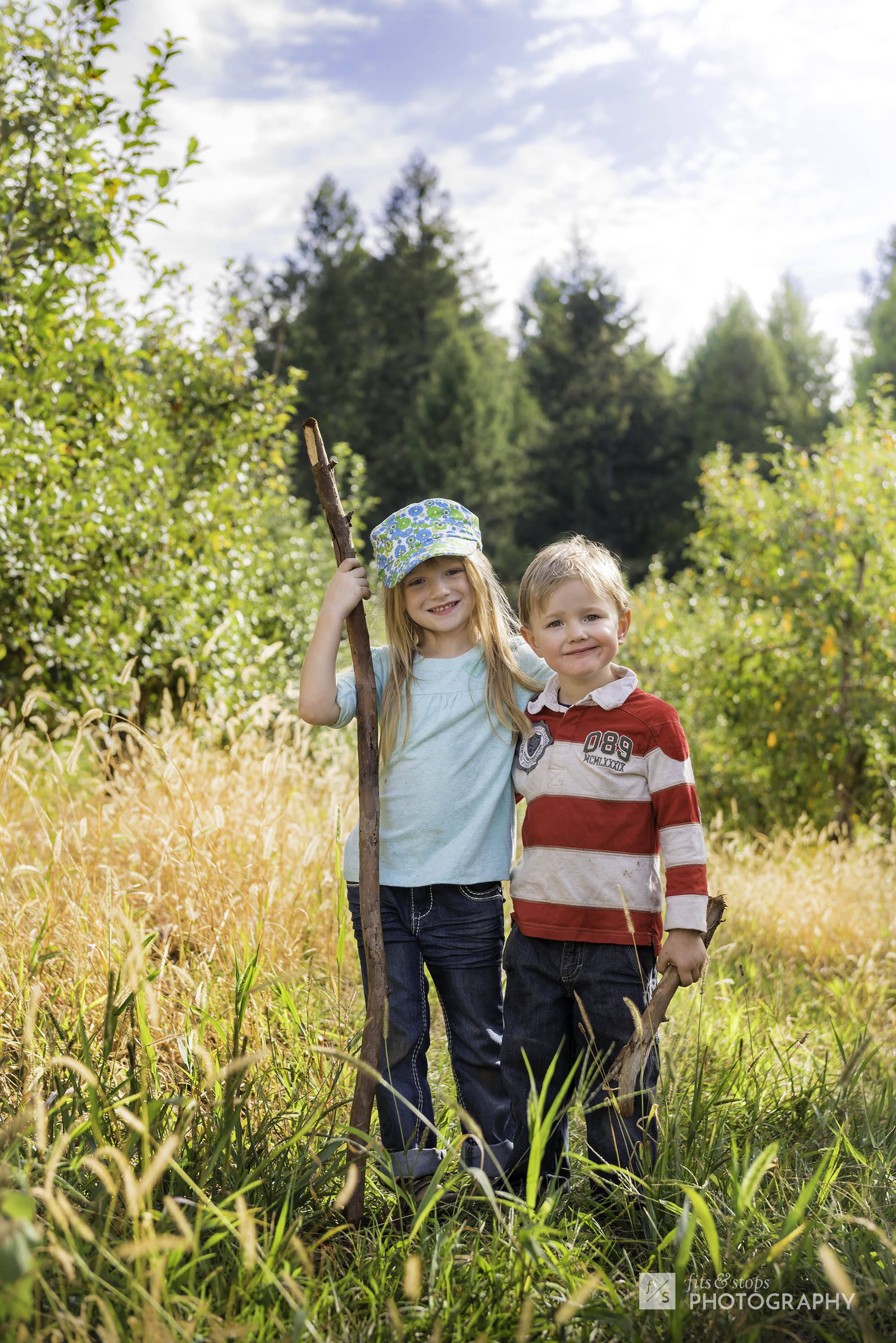 Two young children stand in between rows of apple trees at an orchard in Apple Hill, California.