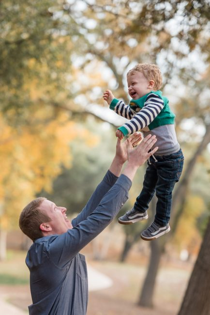 Portrait of a father throwing his son into the air.