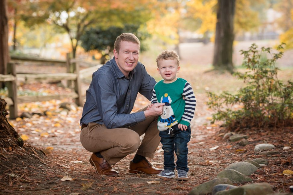A father and son pose for a portrait in the woods