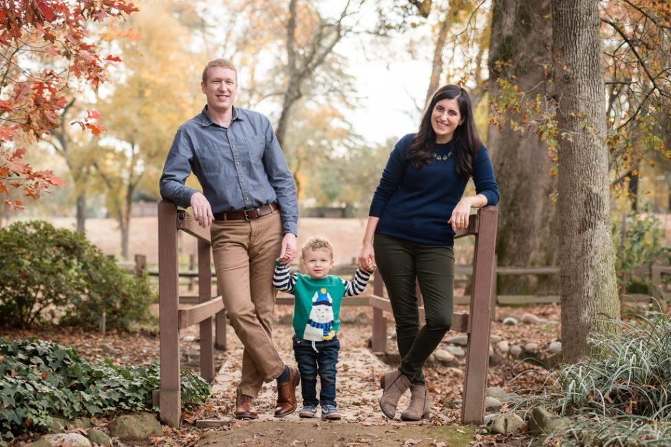 A family of three poses for portraits at Jensen Botanical Gardens