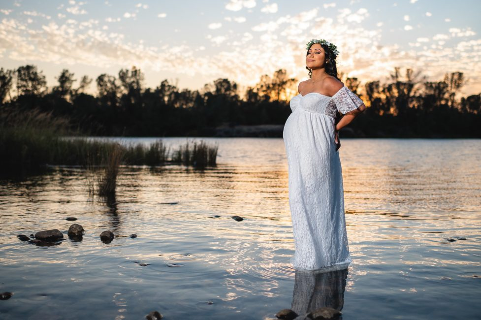 Maternity photo of an Indian woman standing in Lake Natoma
