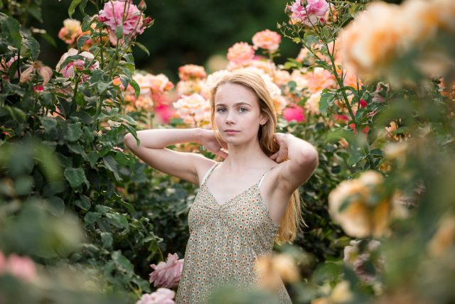 A young woman poses for a senior portrait in the McKinley Park Rose Garden