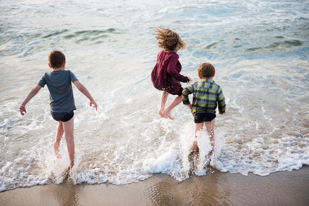 Three children jump over the waves at Marina State Beach.