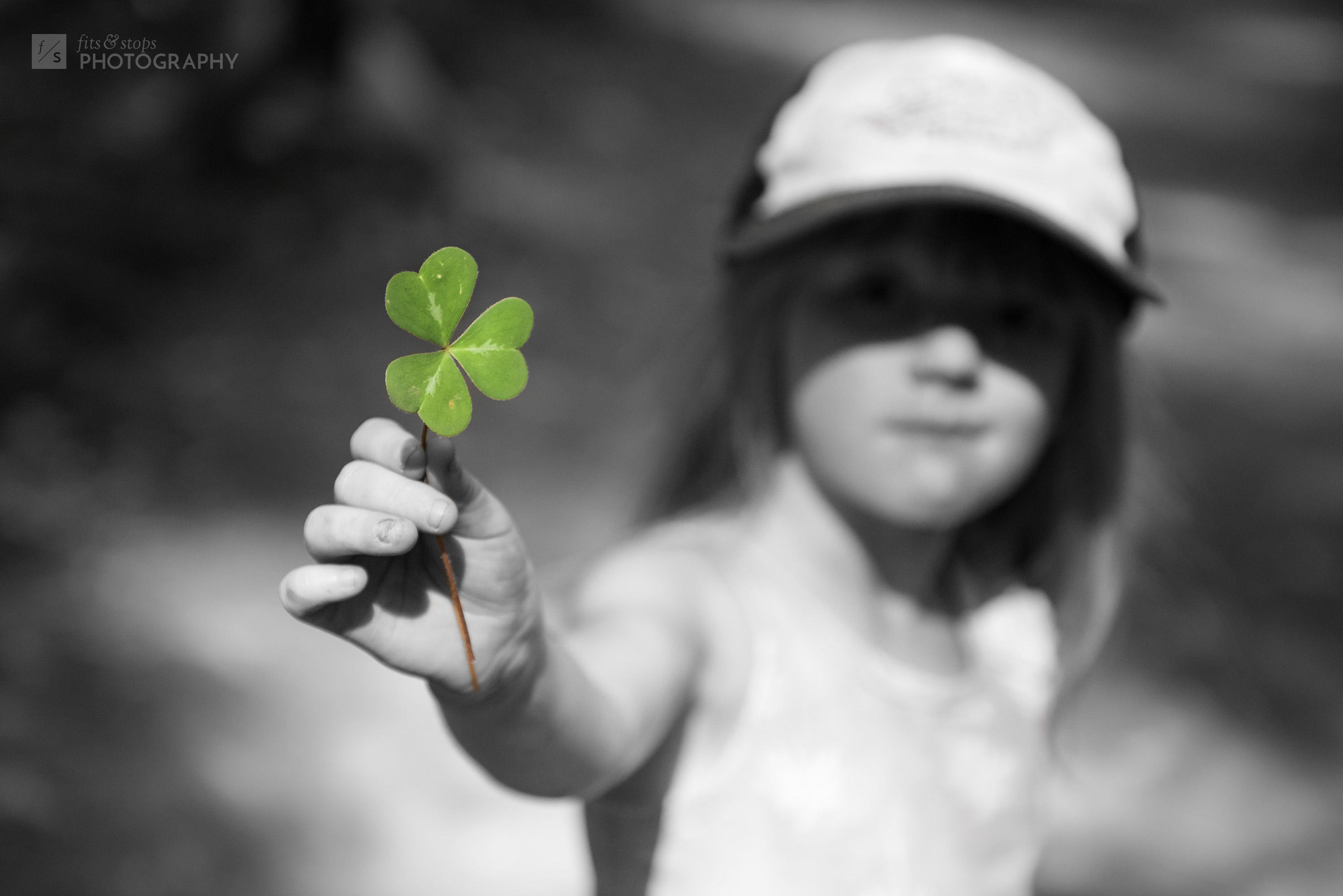 A young girl walks through the forest and discovers a three leaf clover in the trail, holding it up in a shallow DOF photograph. Not lucky, but plenty beautiful.