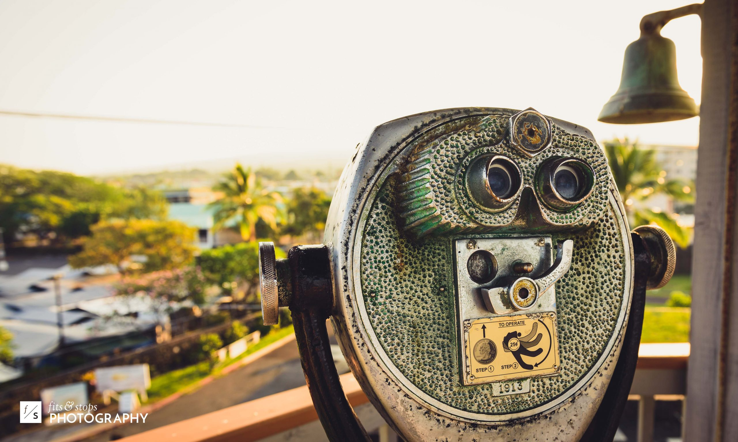 A shallow depth of field photograph of a vintage coin-operated telescope, peering out over a Hawaiian landscape in the town of Kailua.