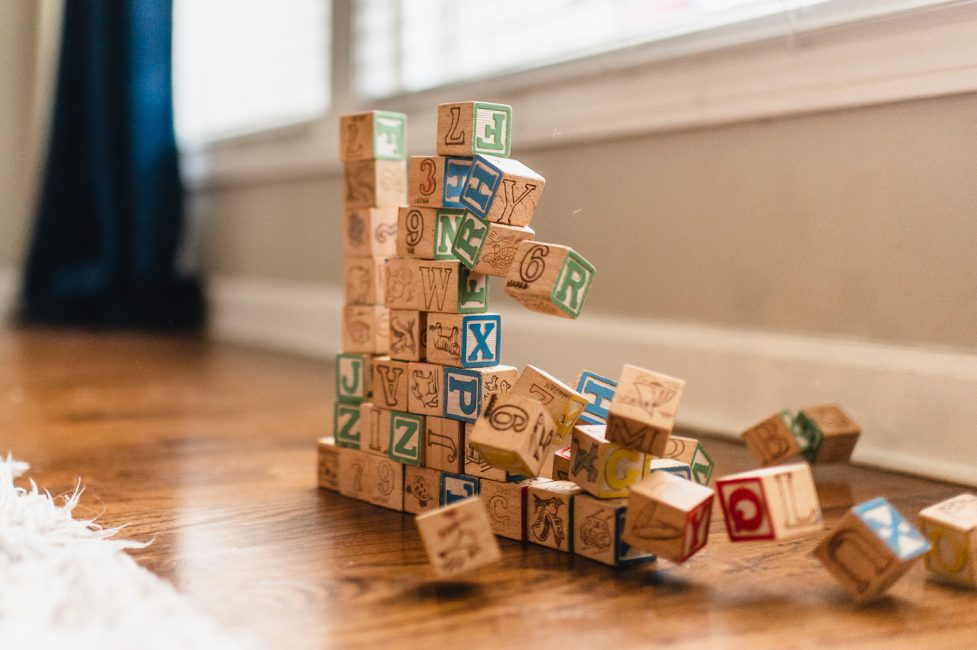 Photograph of a wall of letter blocks collapsing.