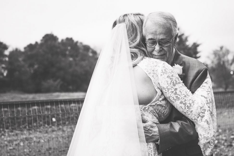 Photograph of a father seeing his daughter in her wedding dress for the first time, overcome by emotion.