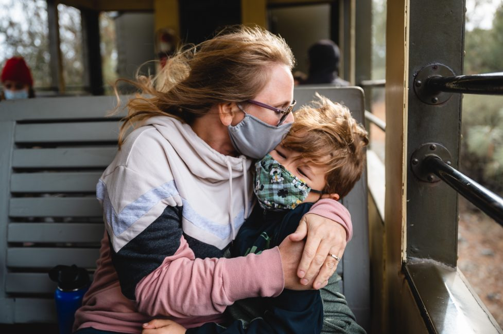 A mother hugs her little boy while wearing masks on a train ride.