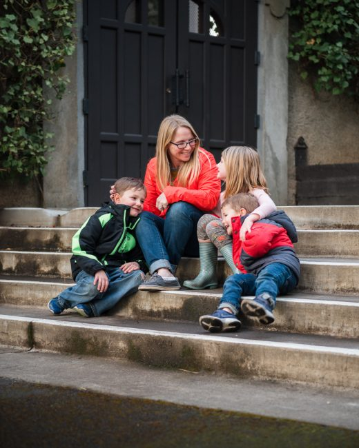 A mother and her three kids sit on the steps of the Elizabethan Theater in Ashland, Oregon.