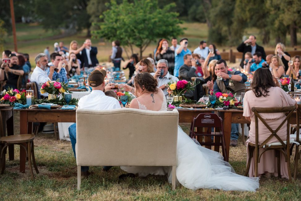 Photograph of a bride and groom toasting as their guests drink on happily