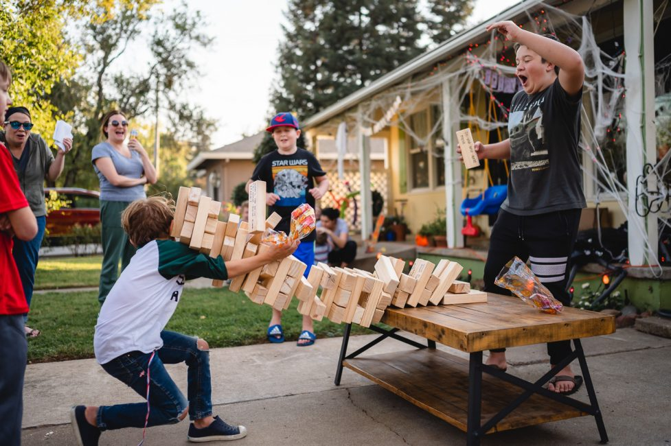 A young boy is hit by a collapsing Jenga tower during a neighborhood party.