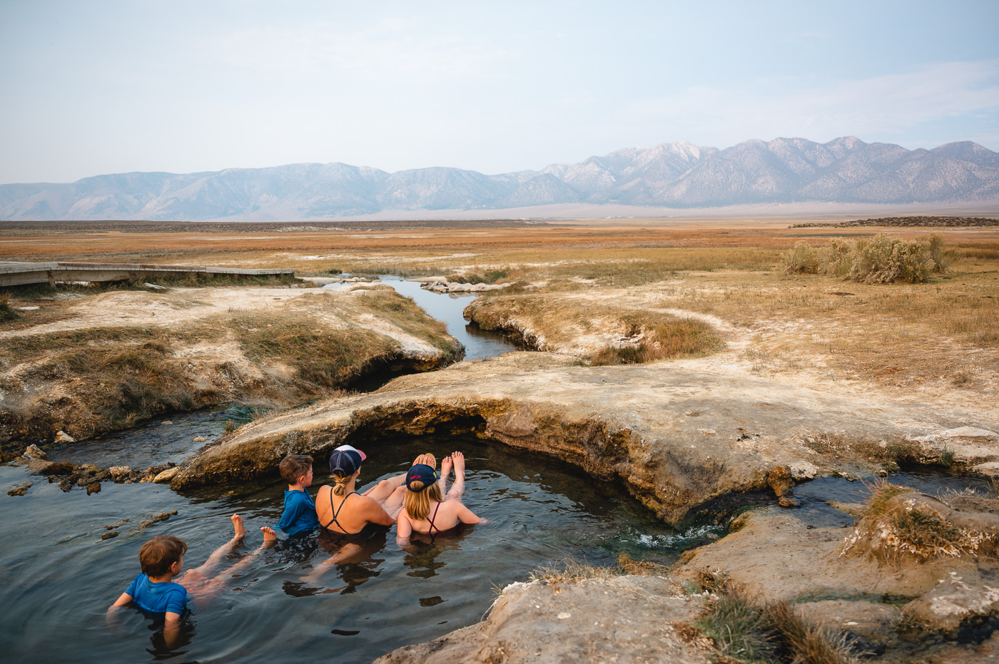 A family sits in natural hot springs near Mammoth Lakes, CA
