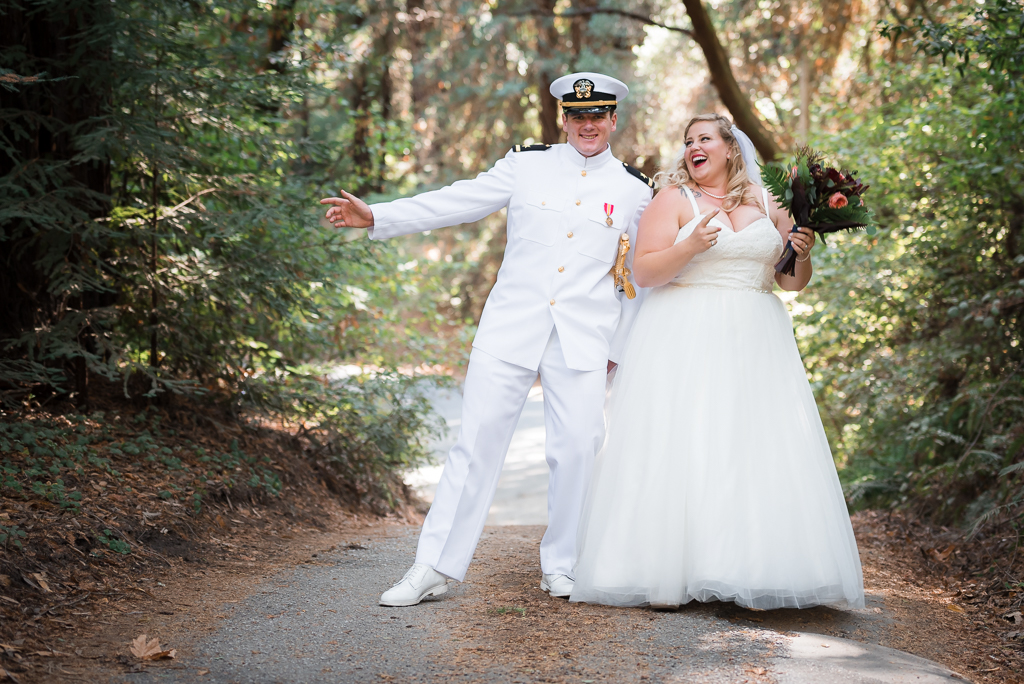 A bride and groom dance their way down a wooded fire road.