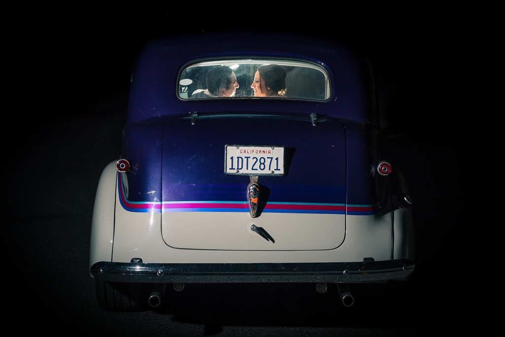 A bride and groom drive away in a restored hot rod at night time.