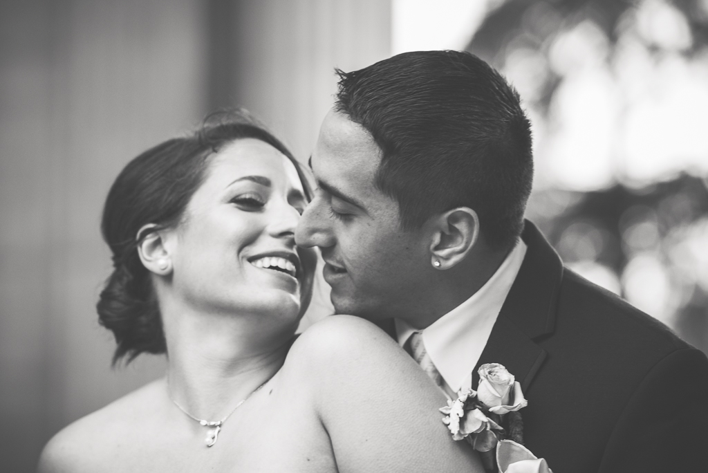 Black and white photo of italian-american newlyweds preparing to kiss.