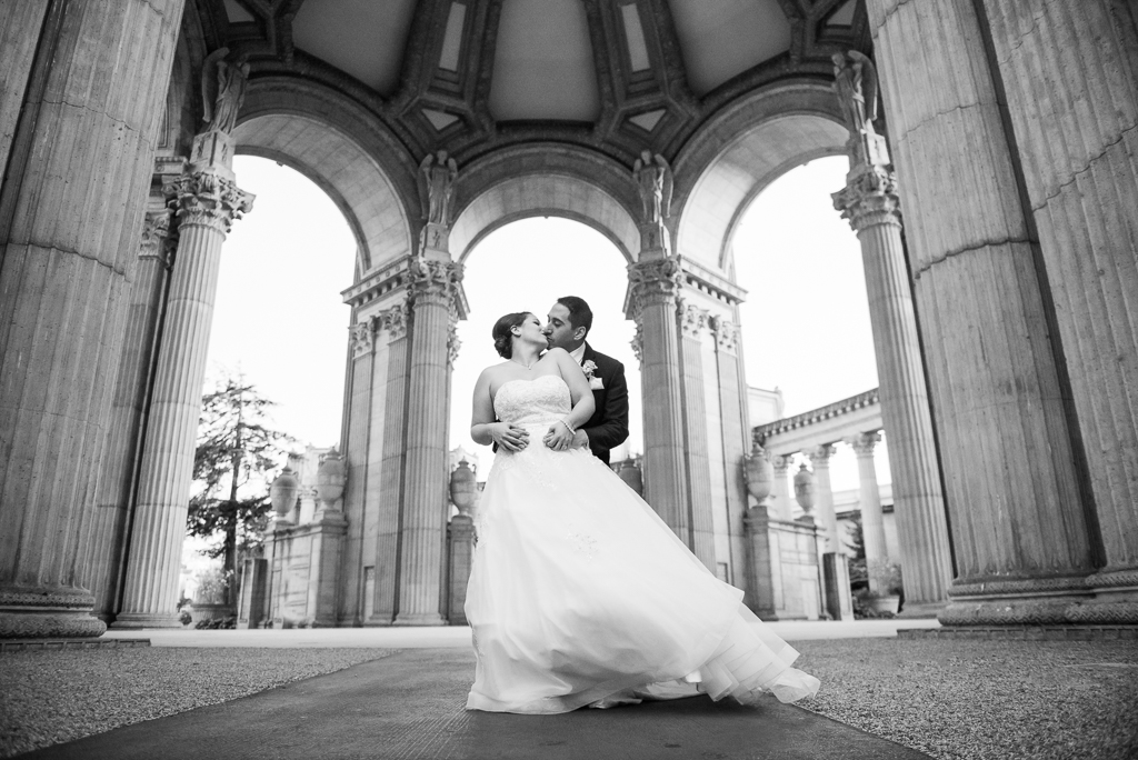 Black and white photo of a bride and groom kissing underneath the dome at the Palace of Fine Arts.