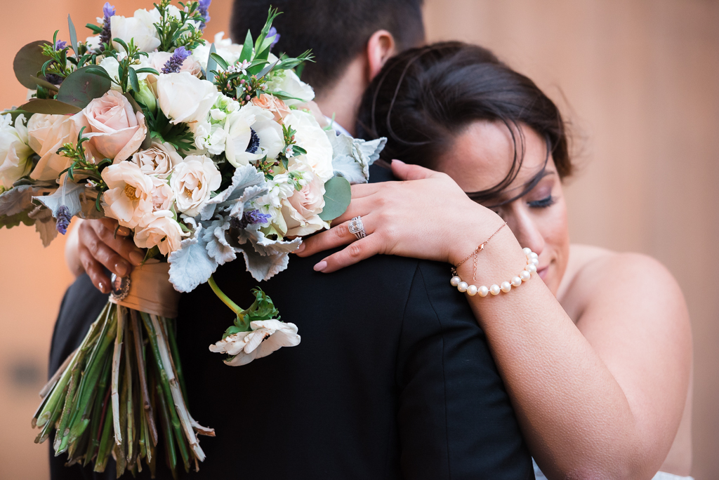 A bride rests against her groom while clutching her bouquet.