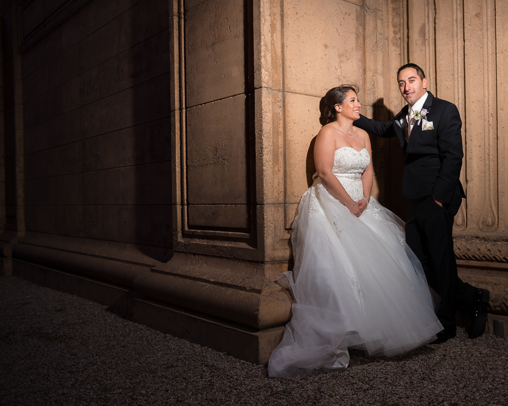Photograph of a bride and groom resting against an ornate wall at the San Francisco Palace of Fine Arts