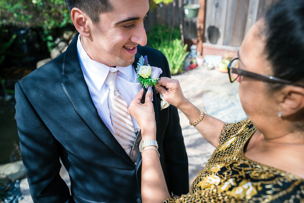 A young italian-american groom watches as his mother pins a bouttonniere on his lapel.