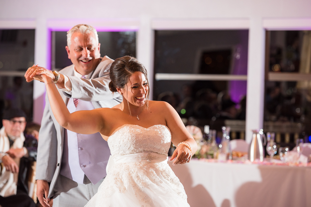 A father twirls his daughter while dancing with her on her wedding day.