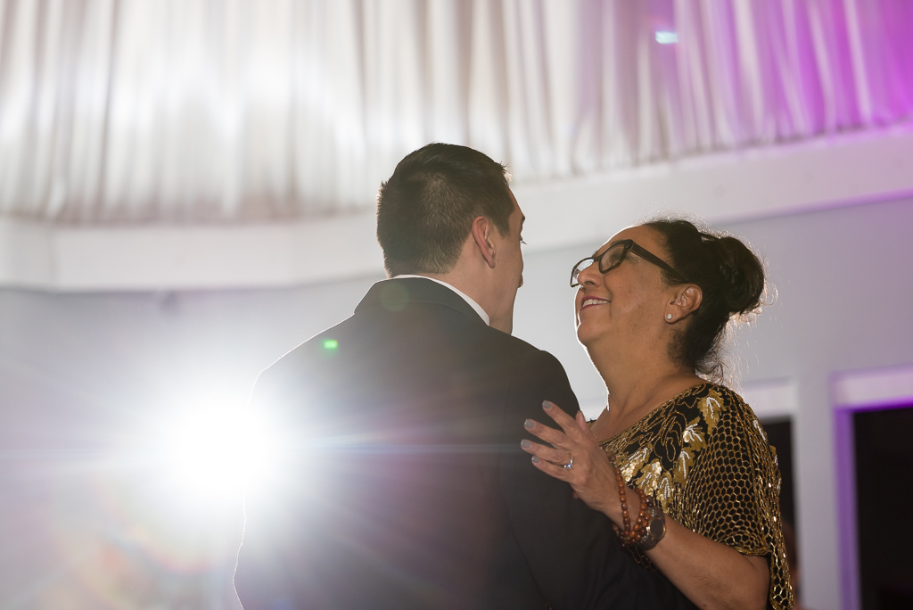Close up photo of a mother dancing with her son at his wedding reception.
