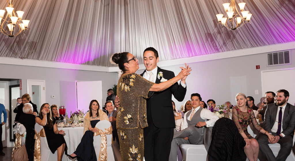 A mother dances with her son on his wedding day at Dominics at Oyster Point.