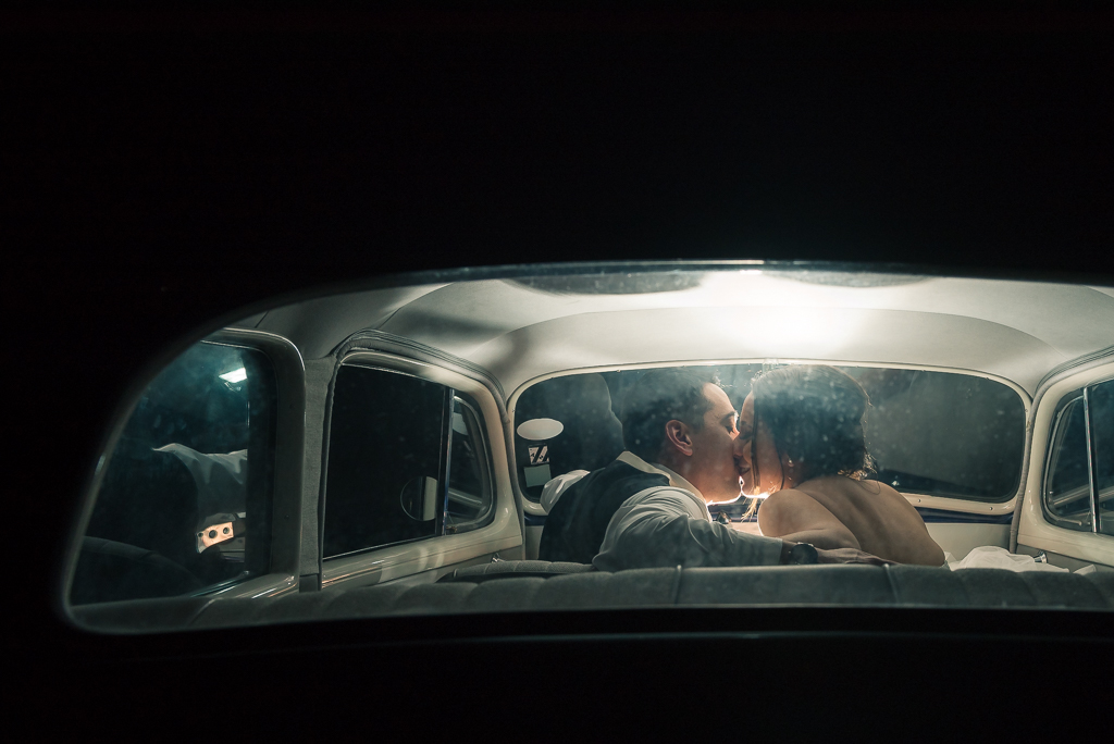 Split-toned photograph of a bride and groom kissing inside a vintage car.