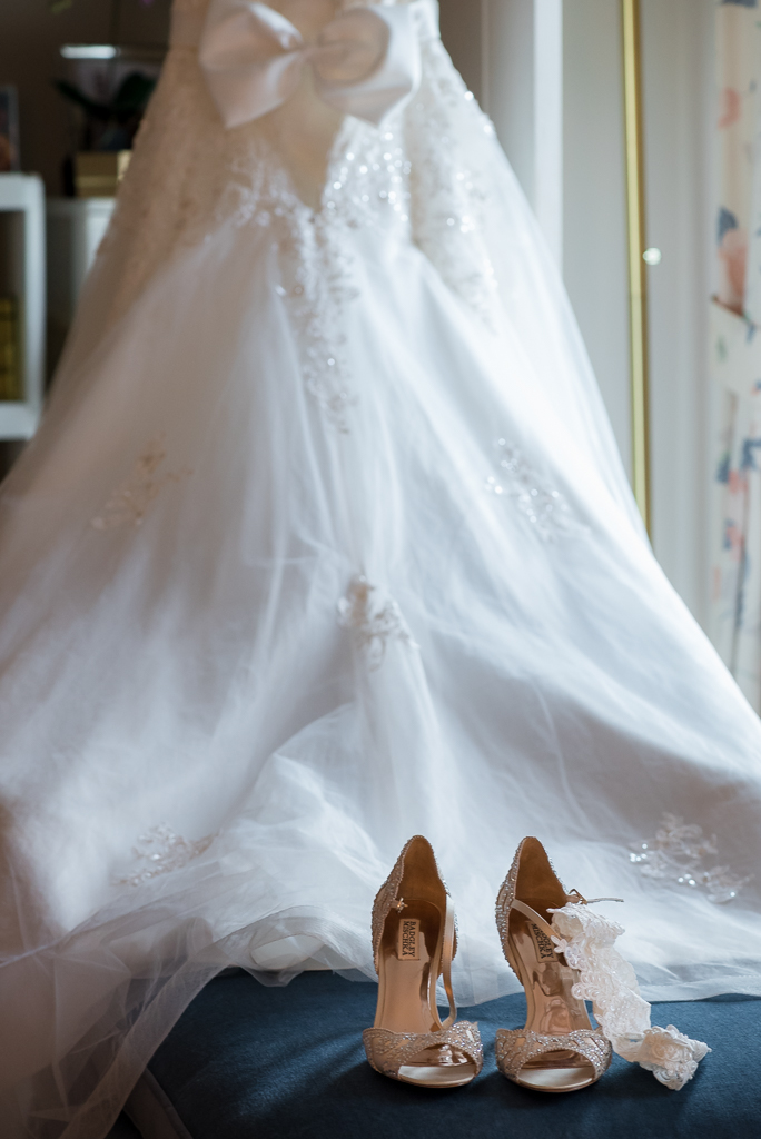 Close up photograph of a wedding dress and heels.
