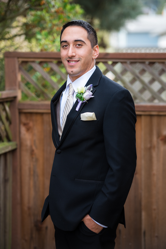 Portrait photograph of a young italian-american groom in a dark suit.