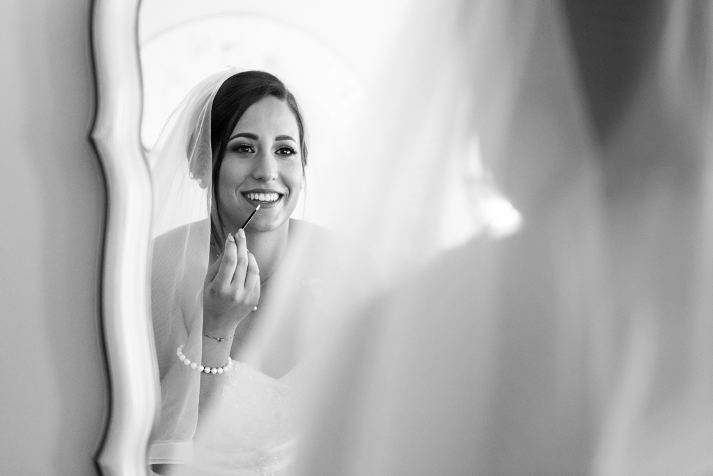 Black and white photograph of a bride applying makeup.