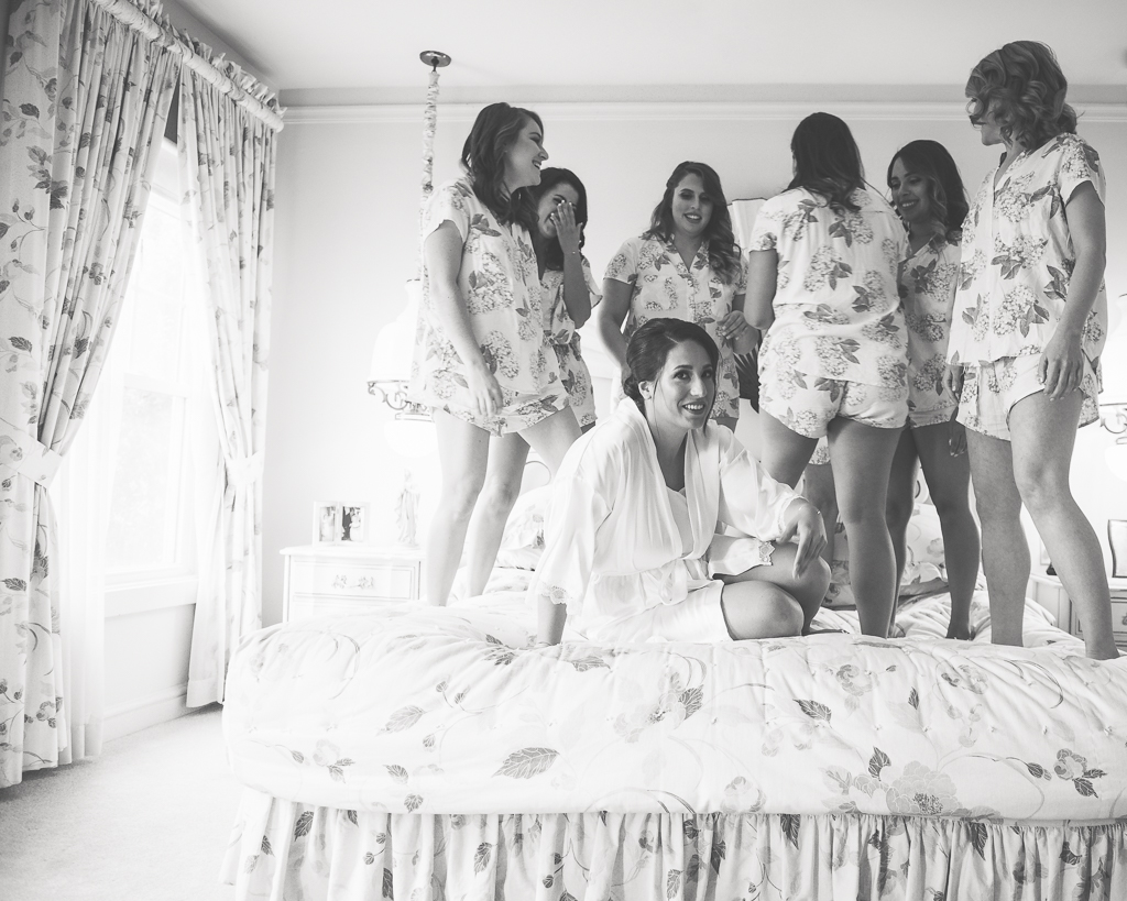 Photo of bridesmaids standing on a bed behind a bride