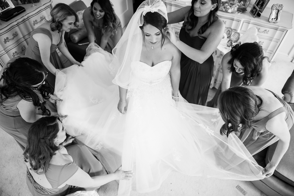 Photo of a bride being dressed and primped by her bridesmaids.