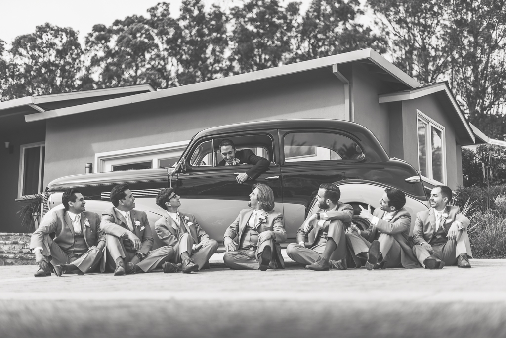 Black and white photograph of groomsmen looking at the groom sitting in a hot rod.