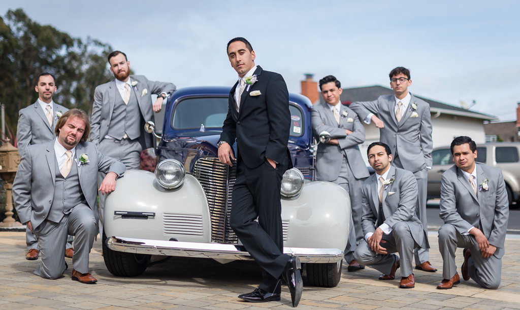 Photograph of a groom and groomsmen posing around an old hot rod.