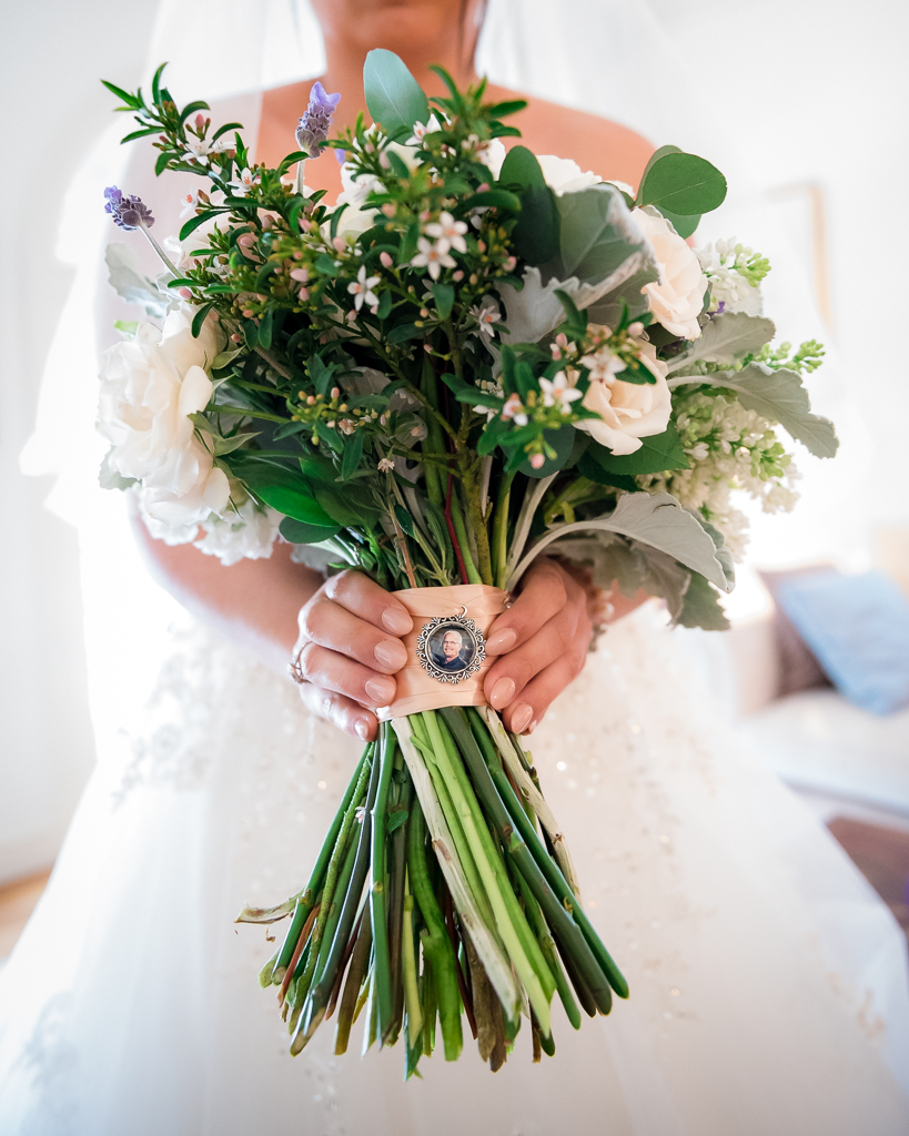 Photo of a bride's bouquet wrapped with a photo in memorial of the groom's father.