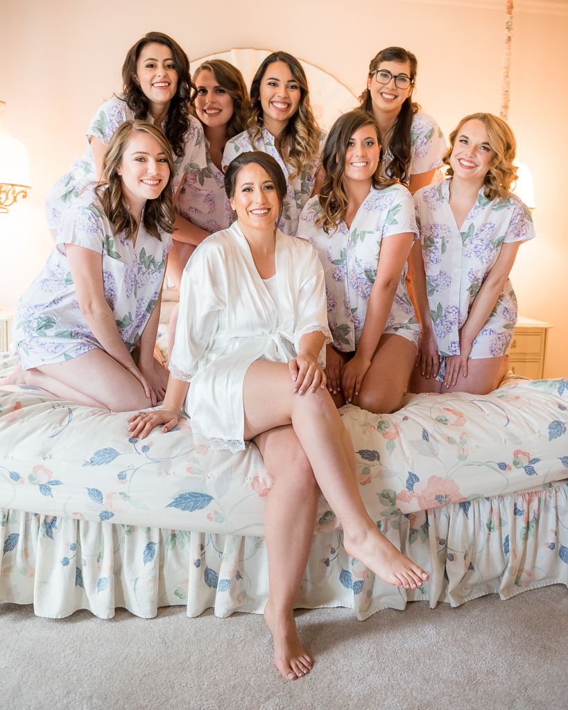 A bride and her bridesmaids huddle together on a bed.