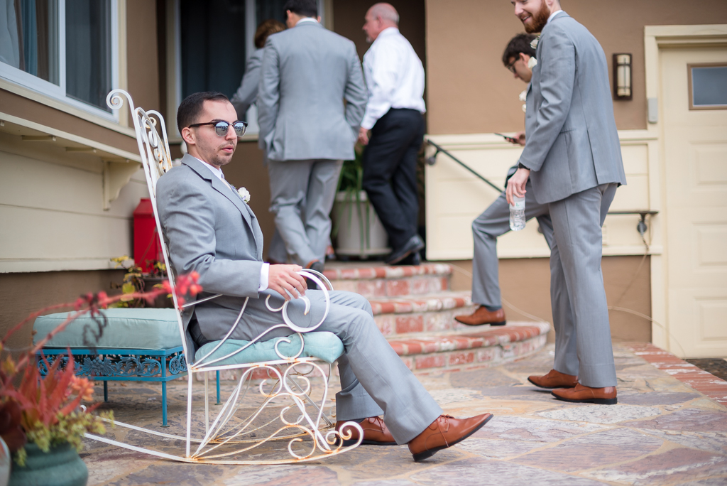 A groomsman sits in an decorative rocking chair following a groomsman portrait session.