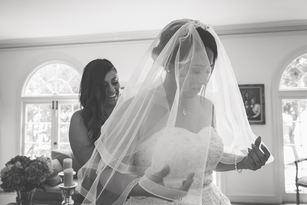 Black and white photo of a maid of honor helping the bride get dressed.