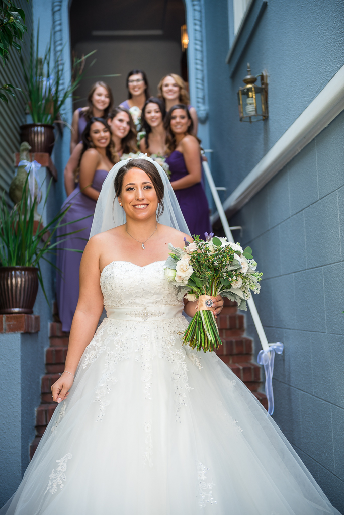 Portrait of a bride walking down an alleyway with her bridesmaids huddled behind.