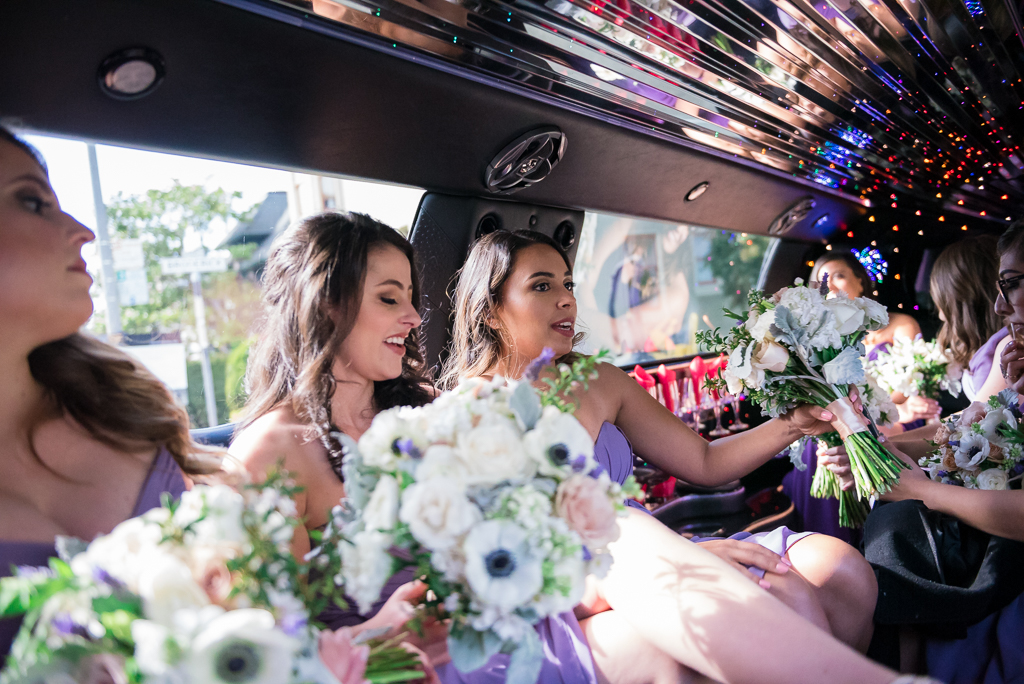 Photo of bridesmaids riding to the church in a limosuine.