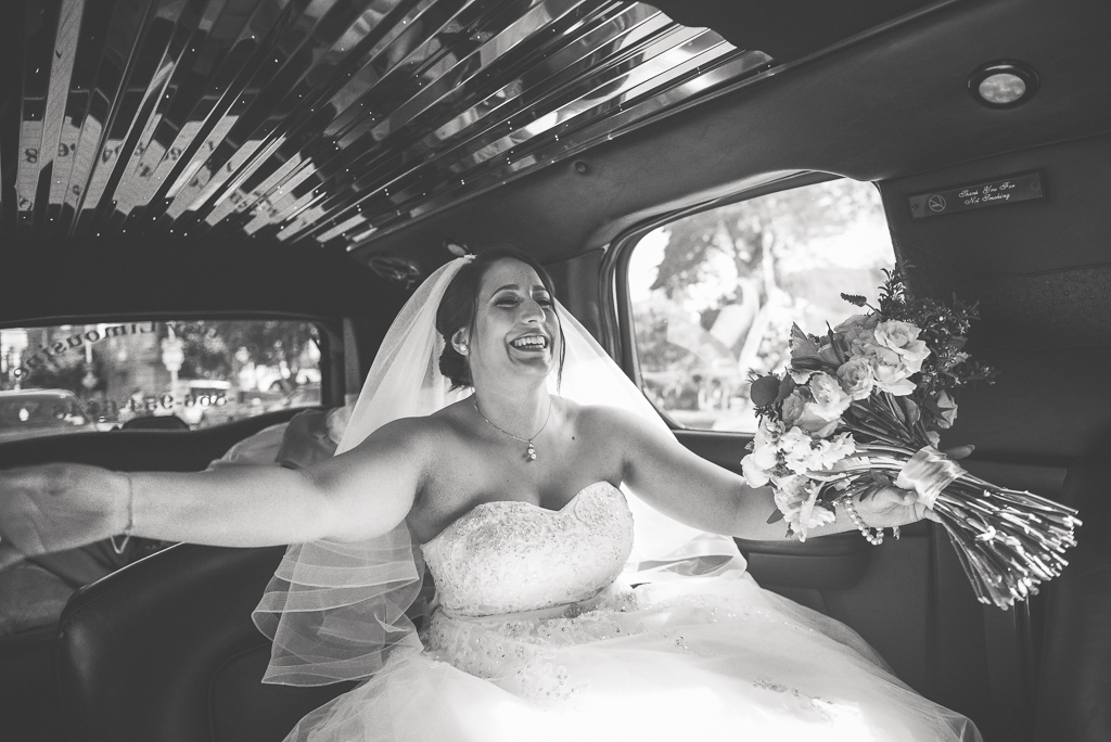 A black and white photo of a bride riding in a limosuine on her wedding day.
