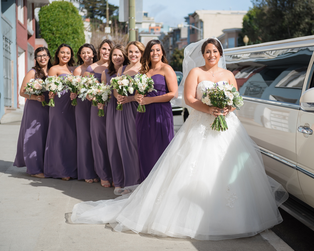 Photo of a Bride with her bridesmaids on hand outside the limo.