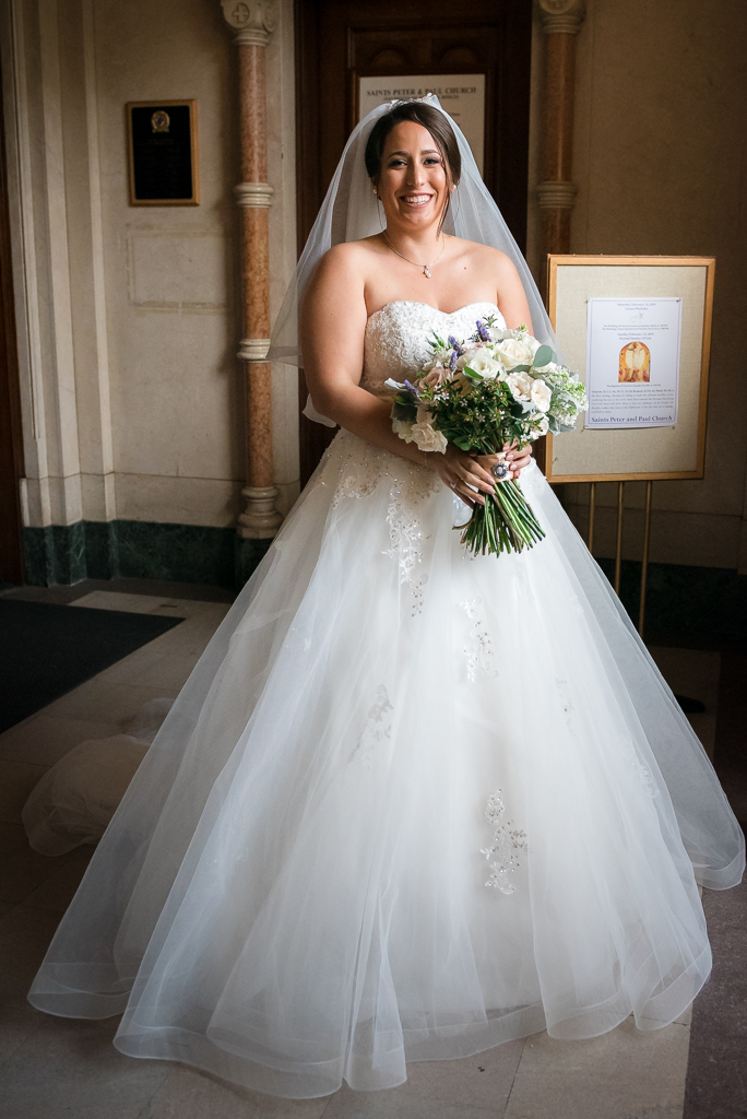 A young italian-american bride poses with her bouquet in the entryway to Saints Peter and Paul Church.